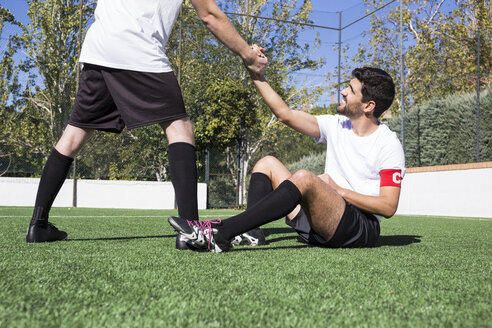 Soccer player helping another player during a soccer match. - ABZF02217