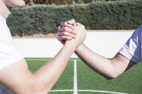Close-up of two football players shaking hands on football field - ABZF02220
