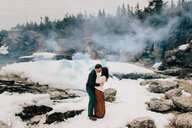 Couple kissing in snow and rock landscape, Tobermory, Canada - ISF20640