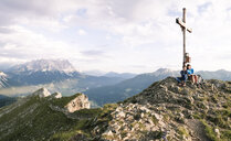 Austria, Tyrol, mother and son on a hiking trip with book at the summit - FKF03253