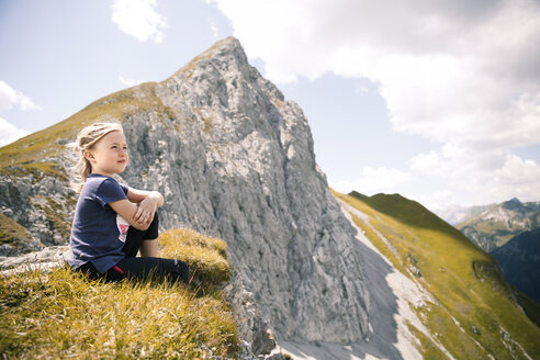 Austria, Tyrol, girl sitting in mountainscape - FKF03256