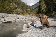 Austria, Tyrol, girl with two dogs at a mountain stream - FKF03262