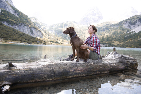 Austria, Tyrol, woman with dog sitting on tree trunk at lake Seebensee - FKF03268
