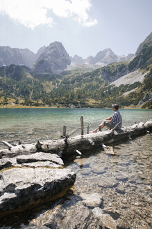 Austria, Tyrol, man sitting on tree trunk at lake Seebensee - FKF03271