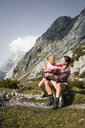 Austria, Tyrol, happy mother with daughter resting in mountainscape - FKF03280
