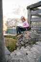 Austria, Tyrol, girl reading book in mountainscape - FKF03283
