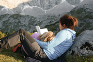 Austria, Tyrol, mother and daughter reading book in mountainscape - FKF03286