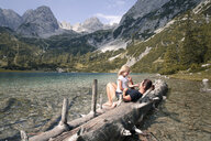 Austria, Tyrol, playful mother and daughter on tree trunk at lake Seebensee - FKF03289