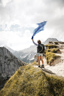 Austria, Tyrol, woman on a hiking trip in the mountains holding cloth - FKF03295