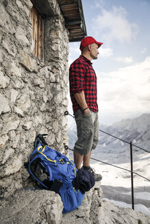 Austria, Tyrol, man on a hiking trip standing at mountain hut looking at view - FKF03322
