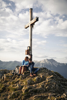 Austria, Tyrol, mother and son on a hiking trip with book at the summit - FKF03328