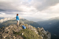 Austria, Tyrol, woman on a hiking trip in the mountains standing on peak - FKF03334