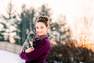Girl hugging french bulldog puppy outdoors - ISF20788