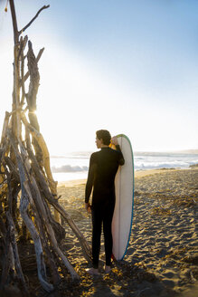Surfer with surfboard on beach, Morro Bay, California, United States - ISF20845