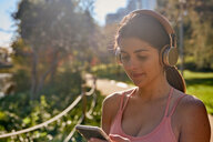 Woman listening to music with headphones in city park - ISF20866