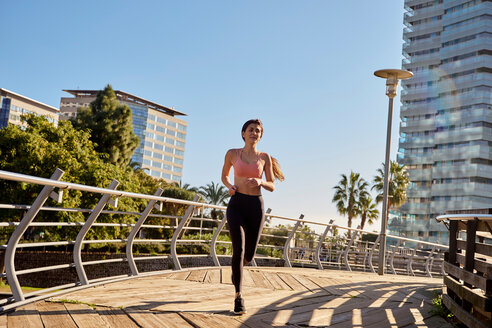 Woman jogging in city park, Barcelona, Catalonia, Spain - ISF20869