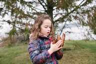 Girl admiring collection of brown pine cones, Kingston, Ontario, Canada - ISF20878