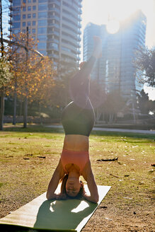 Woman practising yoga in city park, Barcelona, Catalonia, Spain - ISF20896