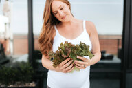 Pregnant woman admiring lettuce - ISF20914