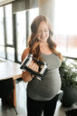 Pregnant woman using weights at home - ISF20923
