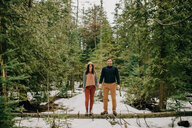 Couple standing on fallen tree trunk in forest, Tobermory, Canada - ISF20935