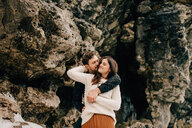 Couple hugging beside rock face, Tobermory, Canada - ISF20944