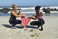 Two women cleaning the beach from plastic waste - ECPF00428