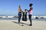 Two women cleaning the beach from plastic waste - ECPF00437