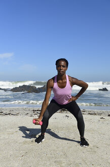Woman doing fitness exercise with dumbbell on the beach - ECPF00449