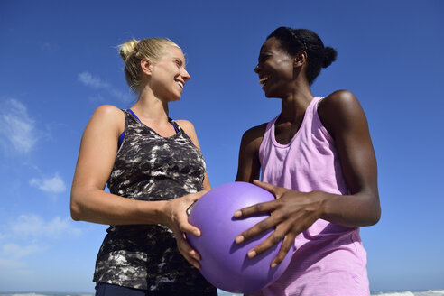 Two happy women holding fitness ball under blue sky - ECPF00452