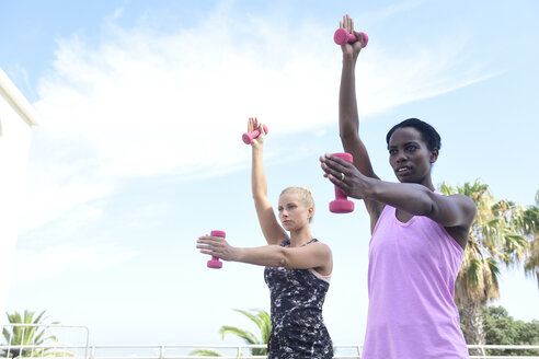 Two women doing fitness exercises with dumbbells outdoors - ECPF00470