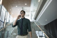 Businessman talking on cell phone on modern office staircase - HEROF21144