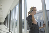 Businesswoman talking on cell phone in sunny office corridor window - HEROF21165