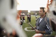 Coach with clipboard talking to teenage boy high school football team on football field - HEROF21225