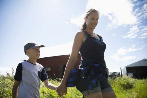 Mother and son holding hands, walking on sunny farm - HEROF21259
