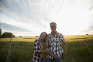 Portrait affectionate couple farmers standing arm in arm on idyllic farm at sunset - HEROF21280