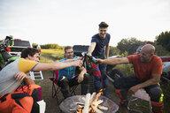 Male friends toasting beer bottles around campfire near motorbikes - HEROF21358