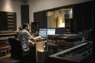 Male music producer working at computer in recording studio - HEROF21370