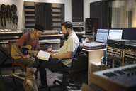 Male music producer and guitarist meeting in recording studio - HEROF21373