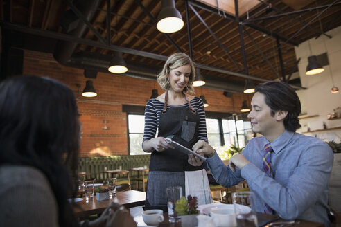 Man paying server, signing bill on digital tablet at restaurant table - HEROF21382