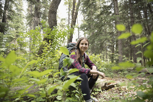 Portrait smiling, confident teenage girl with backpack hiking, resting in woods - HEROF21403