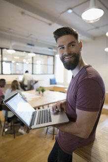 Portrait smiling creative businessman standing, working at laptop and looking over shoulder - HEROF21466