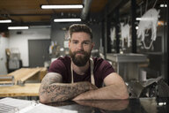 Portrait confident male butcher with tattoos and beard in butcher - HEROF21475
