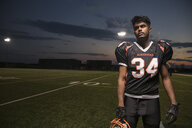 Portrait serious, tough teenage boy high school football player on football field at night - HEROF21493