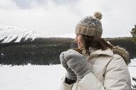 Woman drinking coffee in snowy field below mountain - HEROF21520