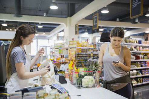 Woman texting at grocery store checkout - HEROF21556