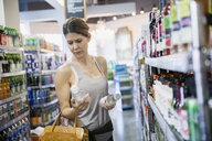 Woman reading labels on bottles in grocery store - HEROF21559