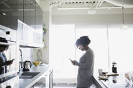 Woman texting with cell phone in morning kitchen - HEROF21610