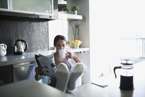 Woman drinking coffee reading magazine with feet up - HEROF21622