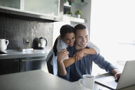 Smiling couple hugging at laptop in kitchen - HEROF21625